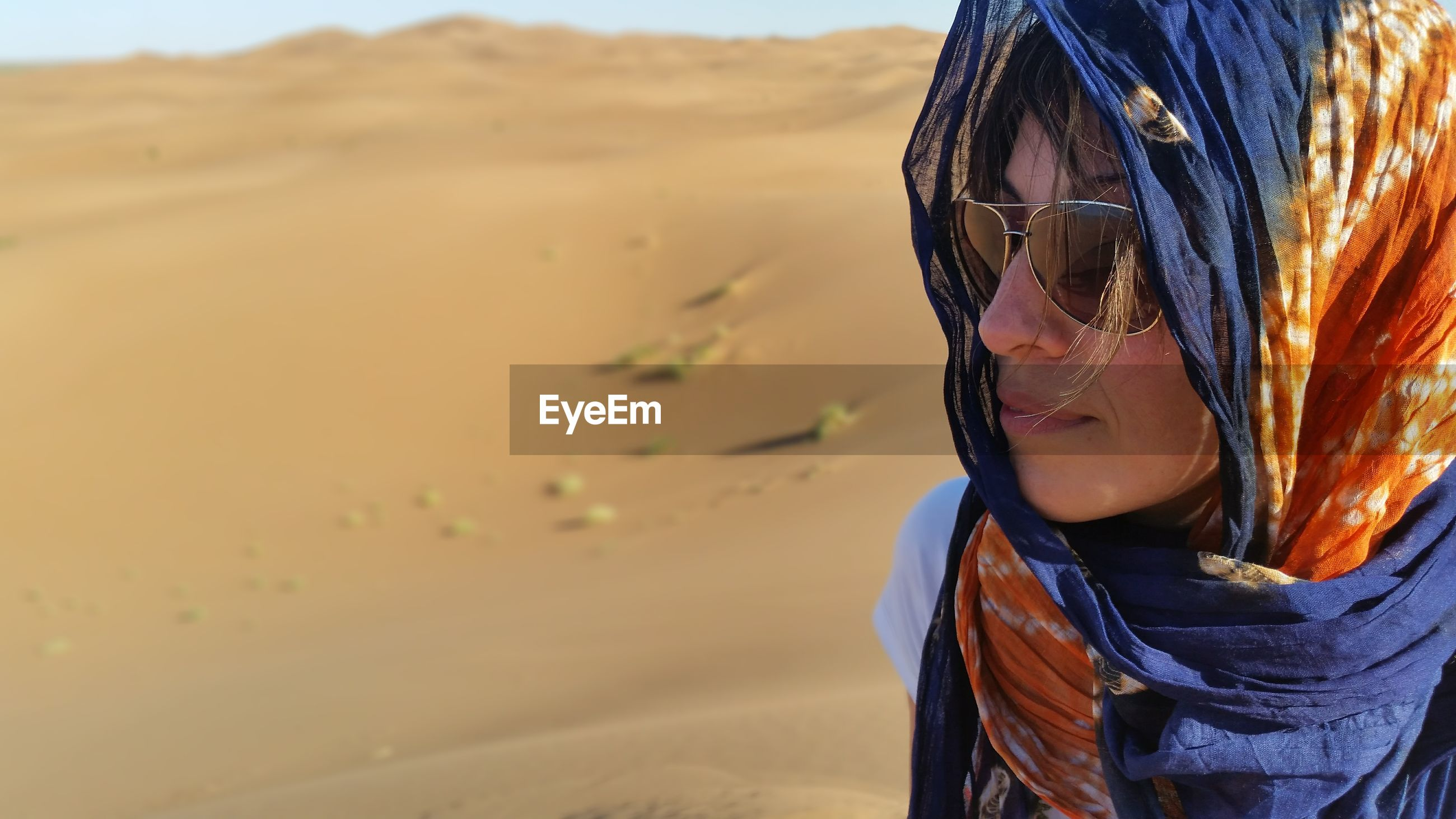 Close-up of woman wearing sunglasses and scarf at desert