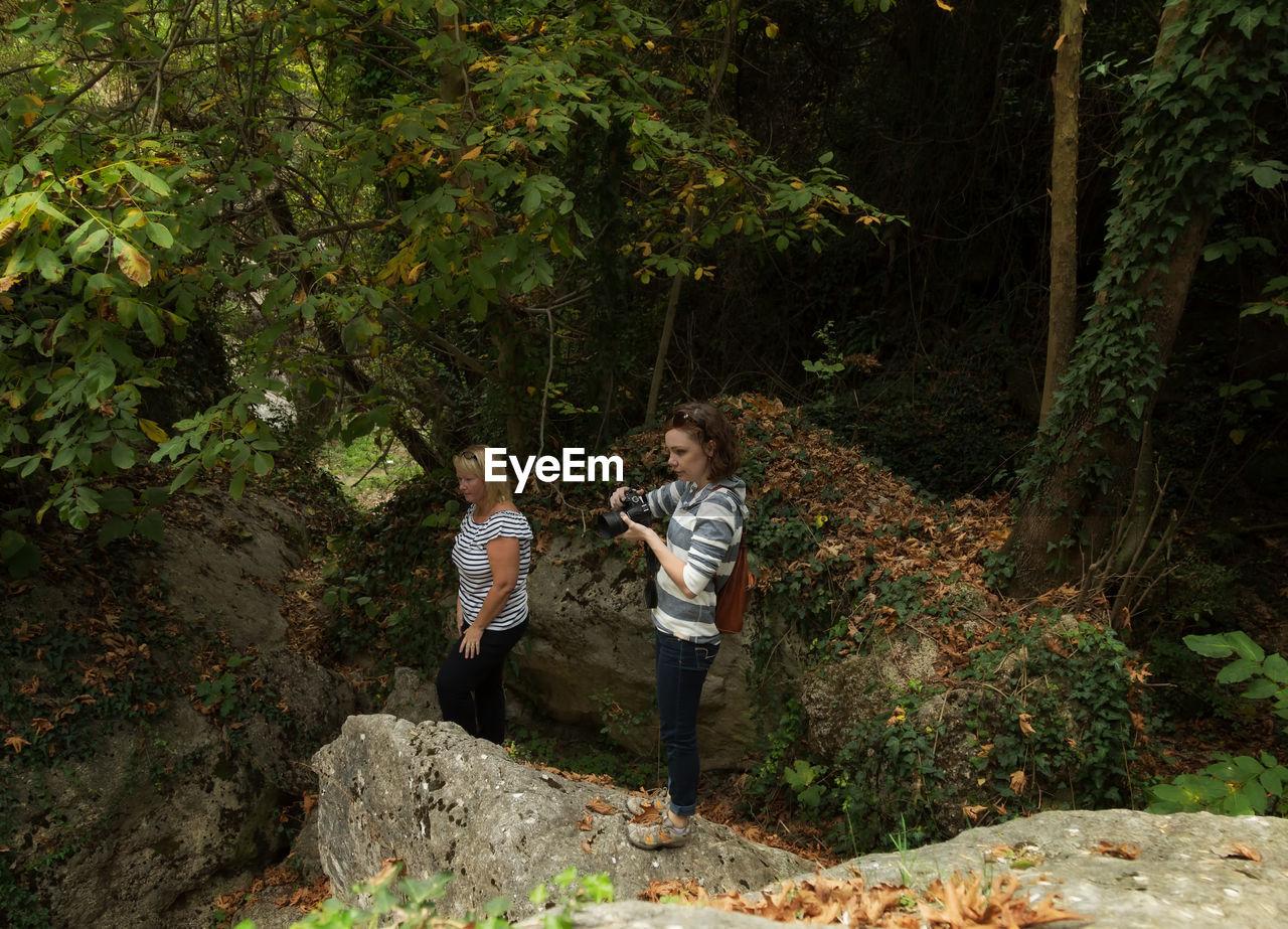 Women standing on rock in forest