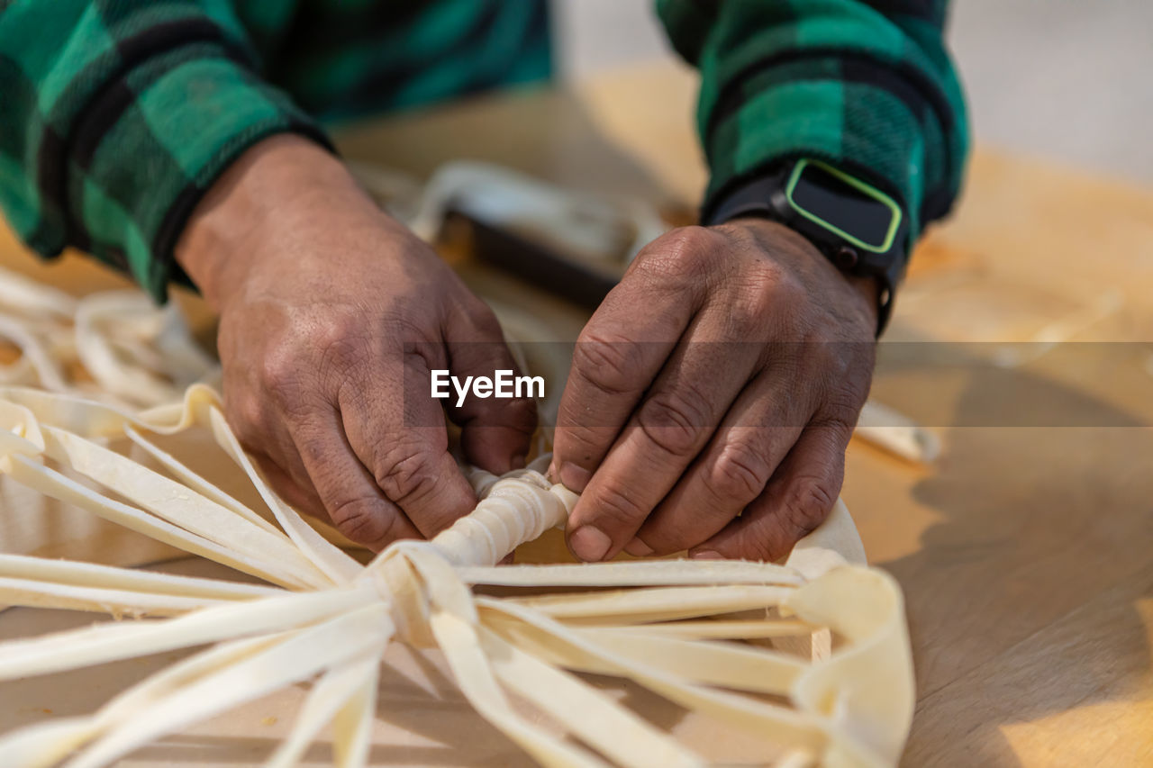 CLOSE-UP OF MAN WORKING ON WOODEN TABLE