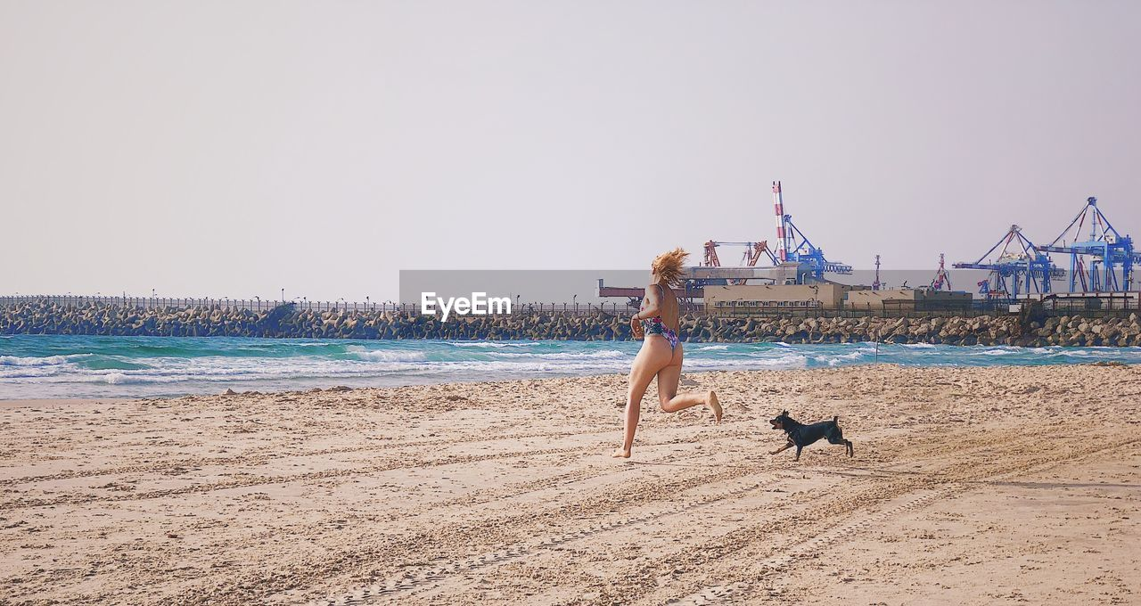 Woman in bikini with dog running on beach against sky