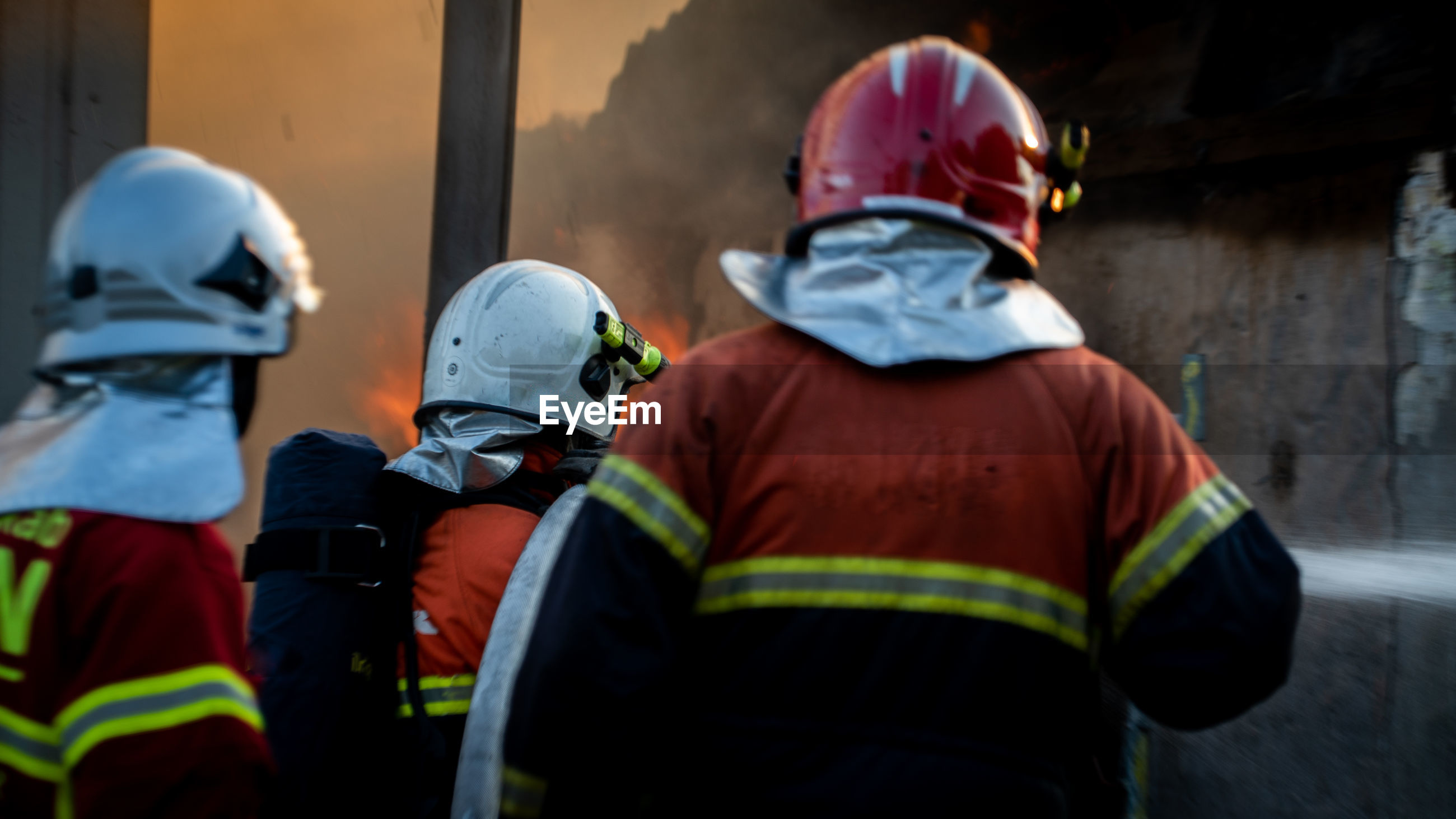 Rear view of firefighters working outdoors