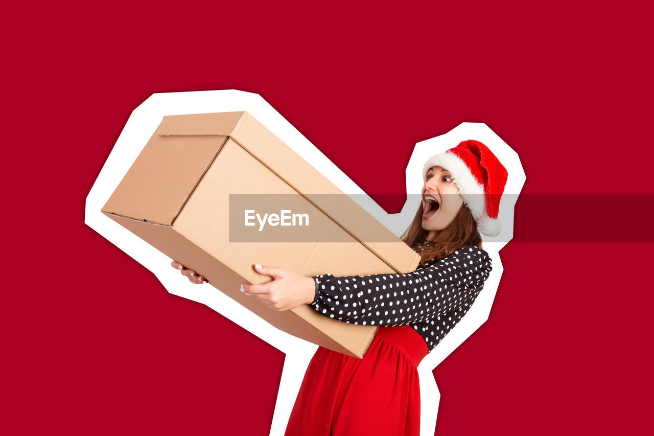 Shocked woman holding box against red background