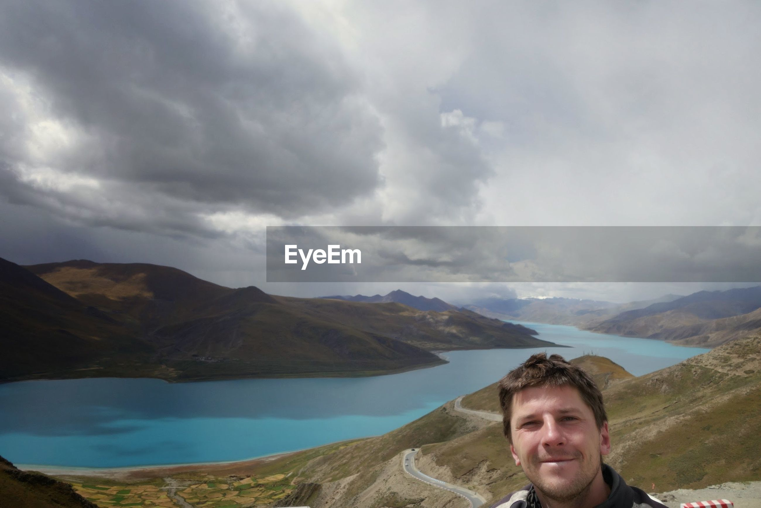 Man on mountain by lake against cloudy sky