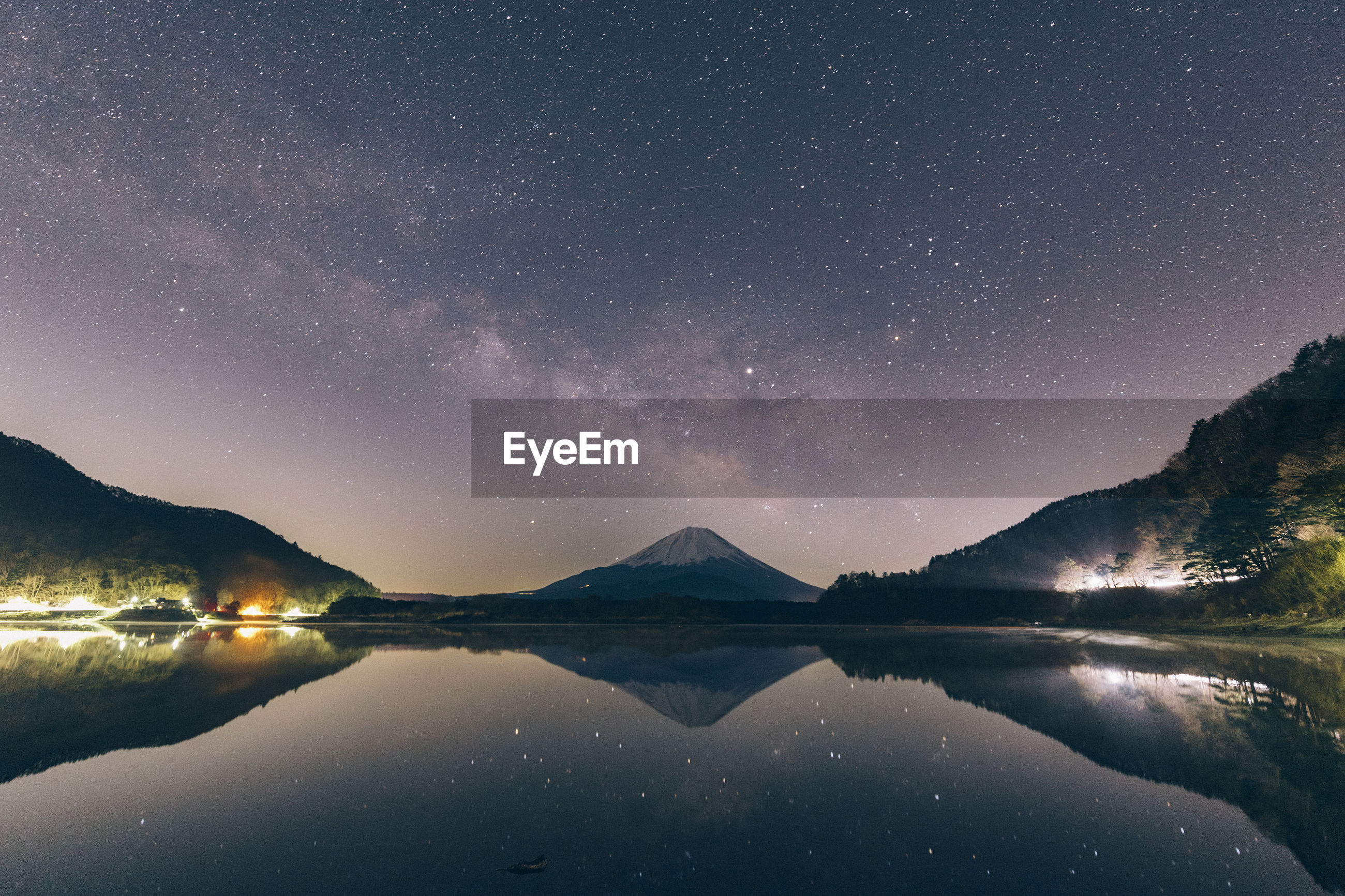 Reflection of mountains in lake against sky at night