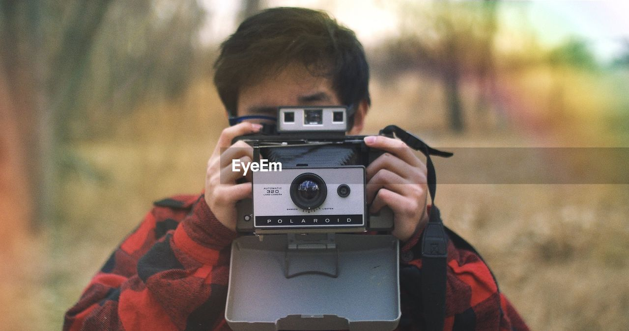 PORTRAIT OF BOY PHOTOGRAPHING OUTDOORS