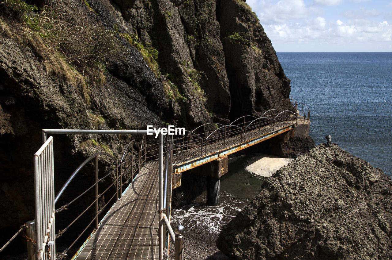 Bridge By Rock Formations Against Sea