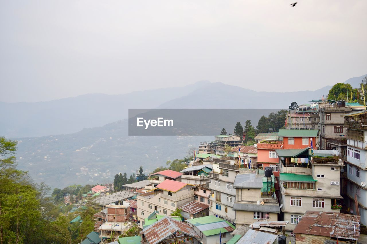 High angle view of town on hill against mountain during foggy weather
