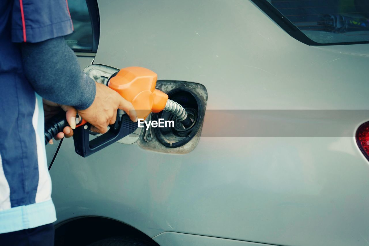 car, motor vehicle, mode of transportation, transportation, land vehicle, one person, refueling, human hand, fuel pump, real people, filling, human body part, hand, gas station, fuel and power generation, holding, day, men, casual clothing, outdoors, human limb