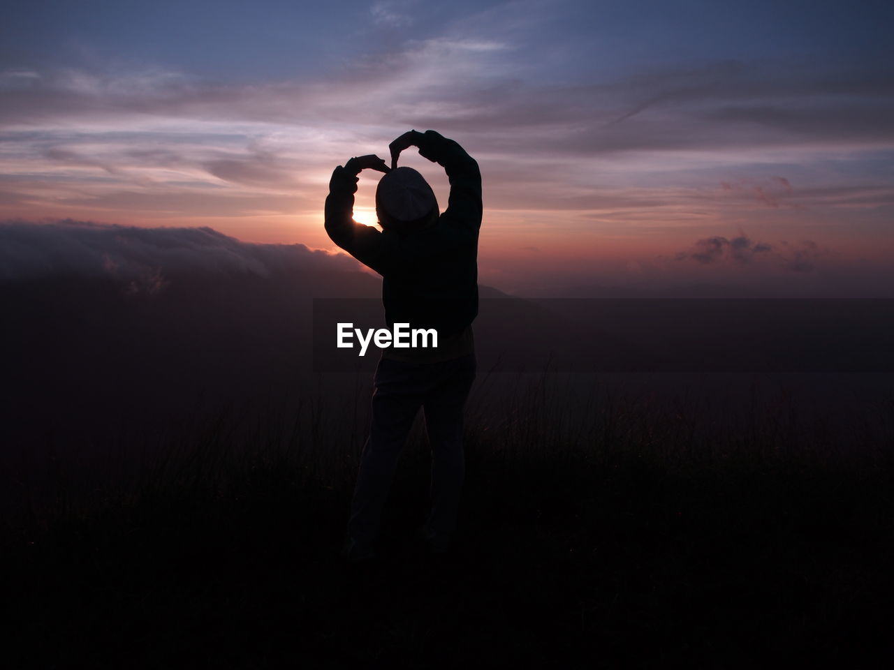 Silhouette woman making heart shape on mountain during sunset