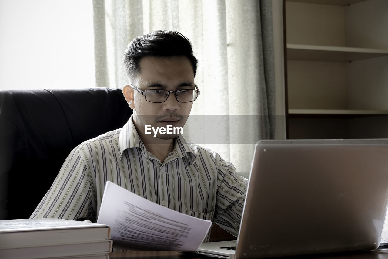 eyeglasses, one person, indoors, technology, laptop, sitting, real people, front view, wireless technology, using laptop, concentration, day, young adult, one man only, only men, reading glasses, adult, people