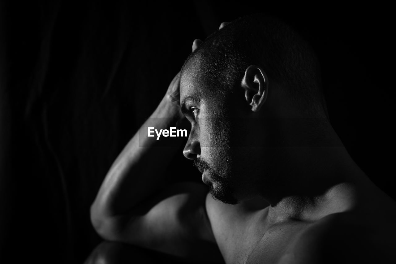 Close-up of shirtless man with hand on head while looking away against black background