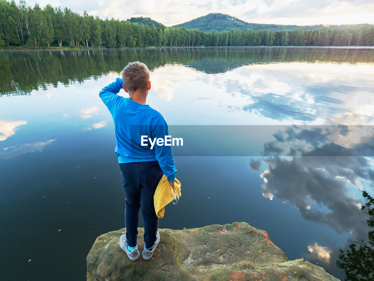 Blue wearing boy with  towel and swimming googles in hands stay on jumping cliff above lake water