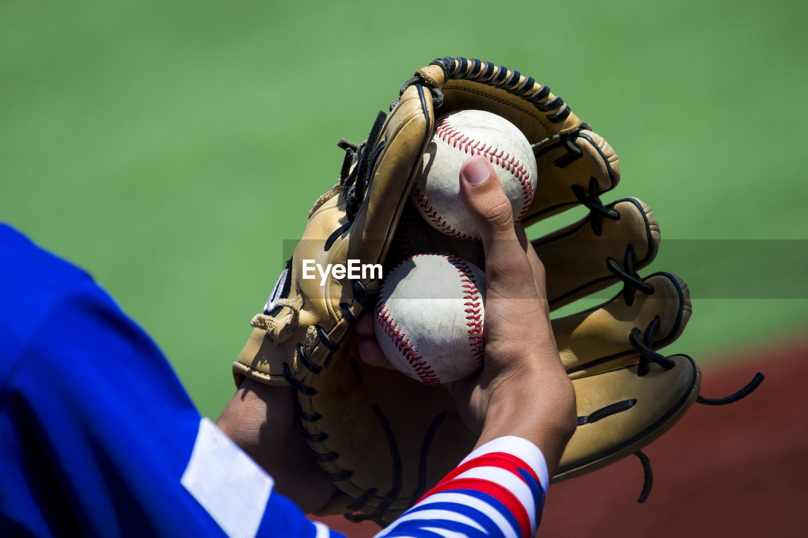 Midsection of baseball player holding glove and balls
