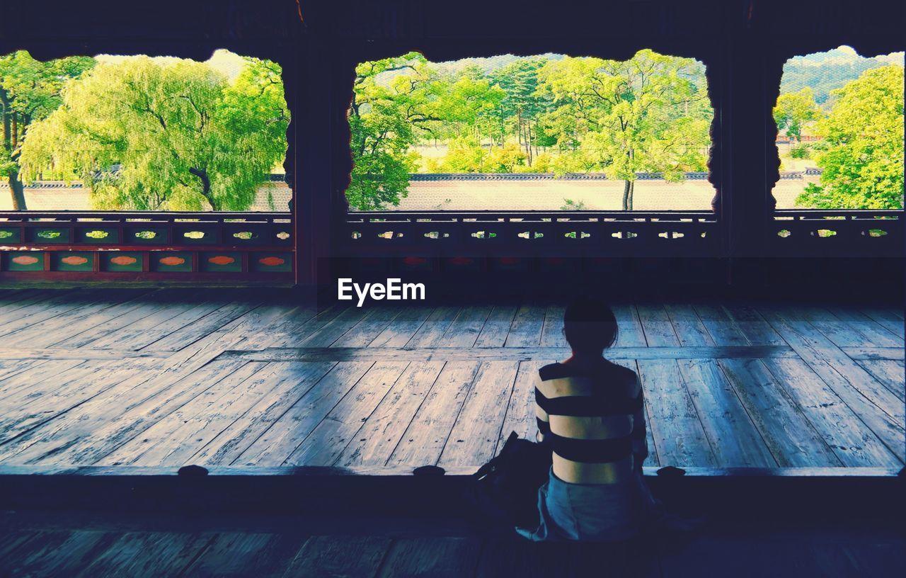Woman meditating in empty buddhist hall