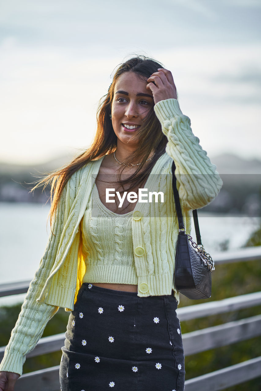 Smiling woman looking away while standing outdoors