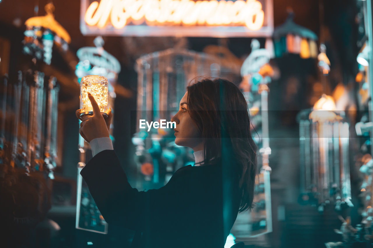 illuminated, one person, young adult, women, retail, leisure activity, focus on foreground, adult, young women, store, lifestyles, lighting equipment, night, looking, real people, waist up, shopping, architecture, headshot, retail display, hairstyle, beautiful woman