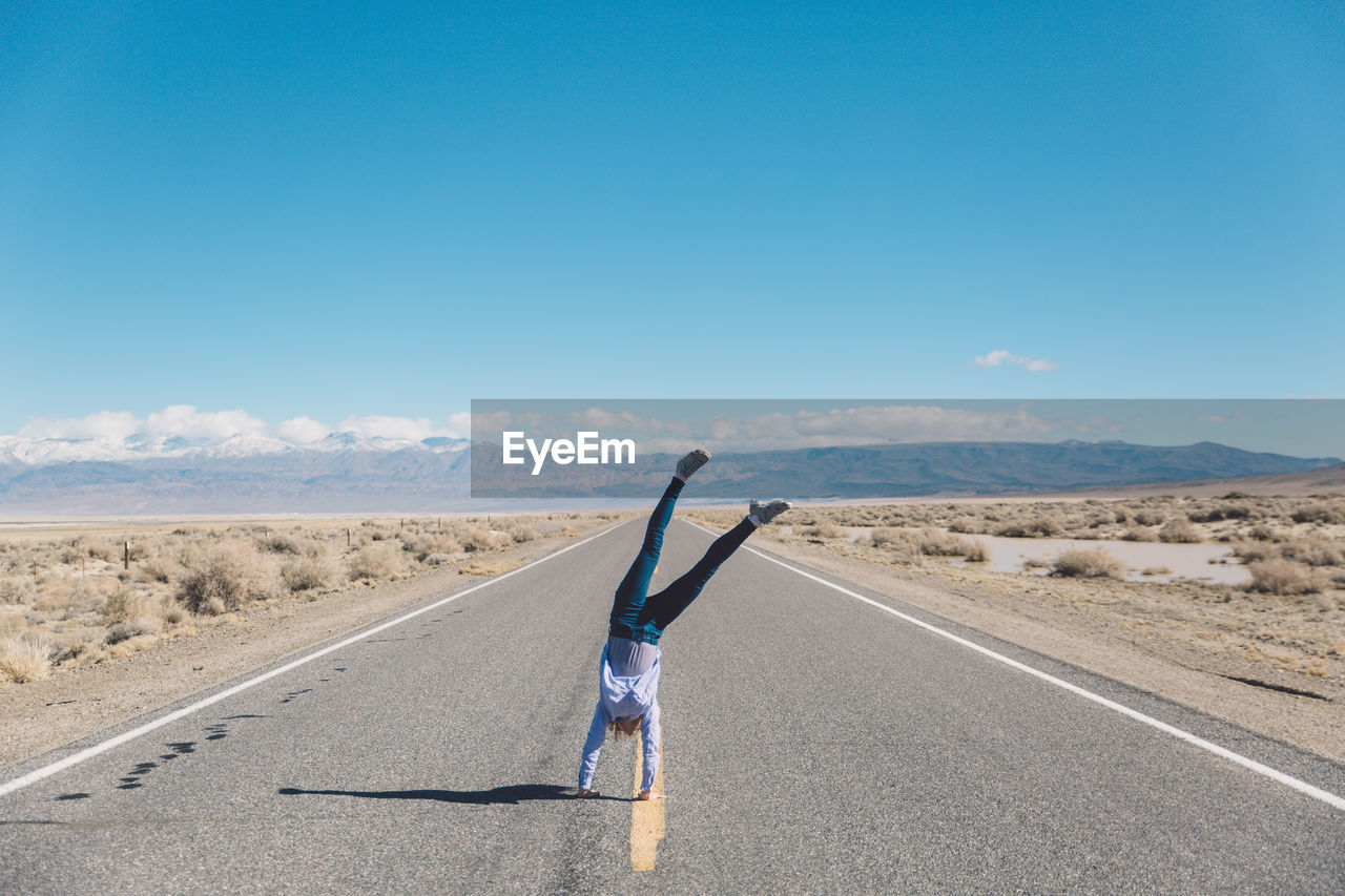 Woman Doing Handstand On Road