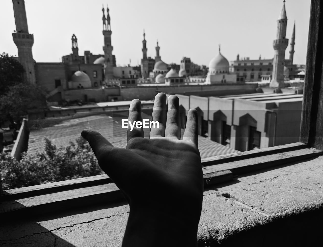 human hand, architecture, built structure, hand, one person, building exterior, human body part, place of worship, human finger, city, finger, building, body part, real people, lifestyles, personal perspective, nature, religion, day, spirituality, outdoors, spire