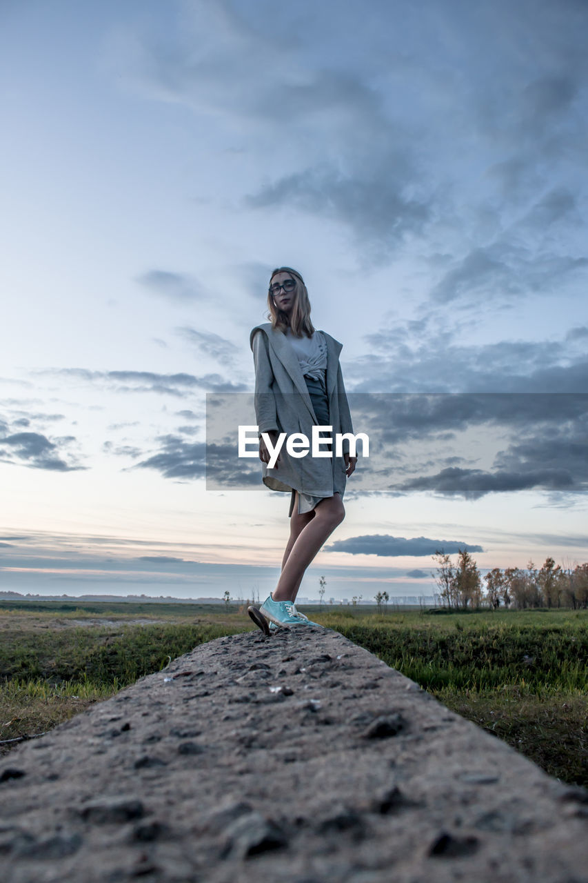one person, sky, full length, cloud - sky, real people, young adult, standing, leisure activity, nature, lifestyles, front view, casual clothing, young women, scenics - nature, day, beauty in nature, land, smiling, outdoors