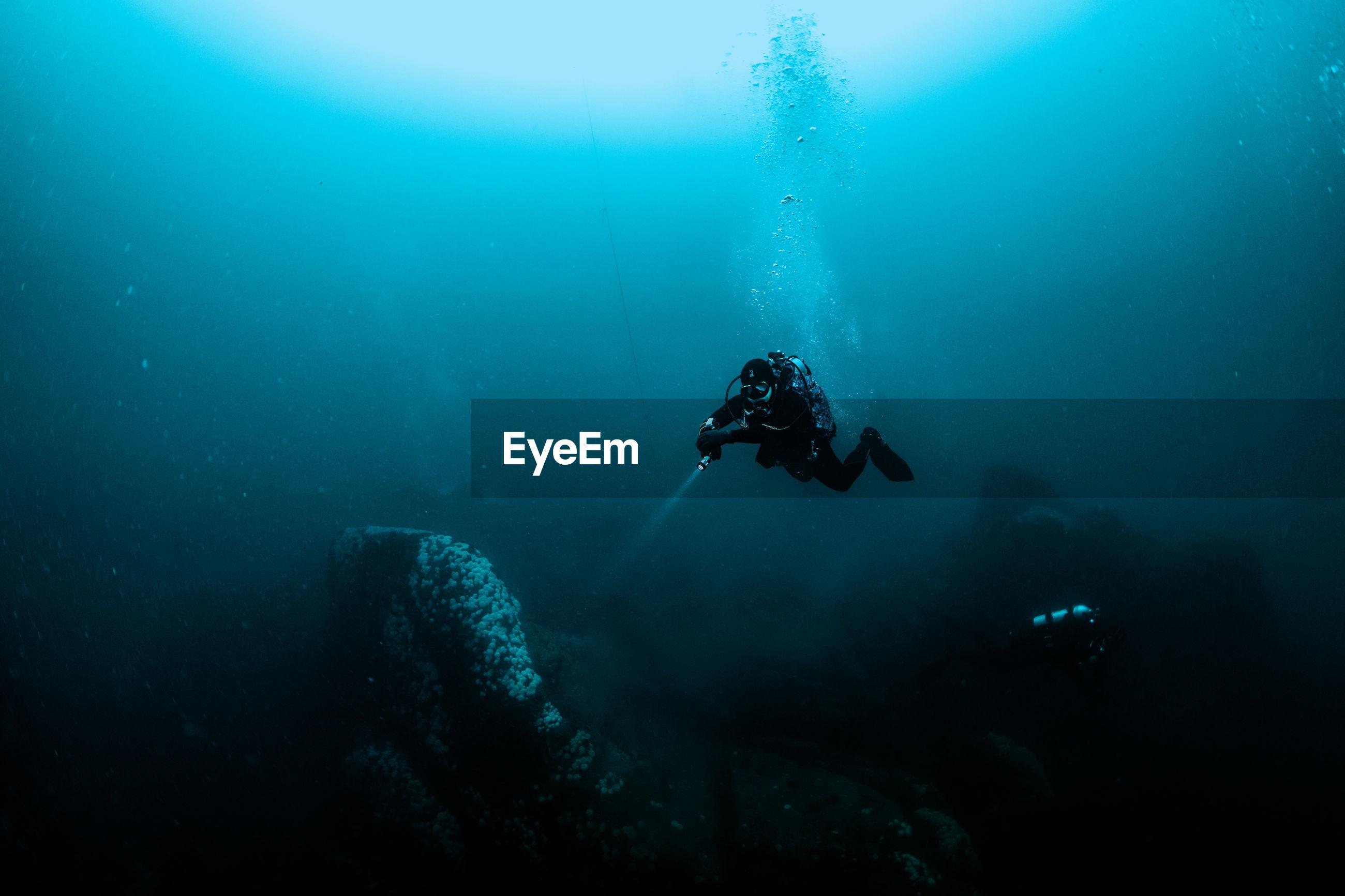 Woman with flashlight swimming in sea