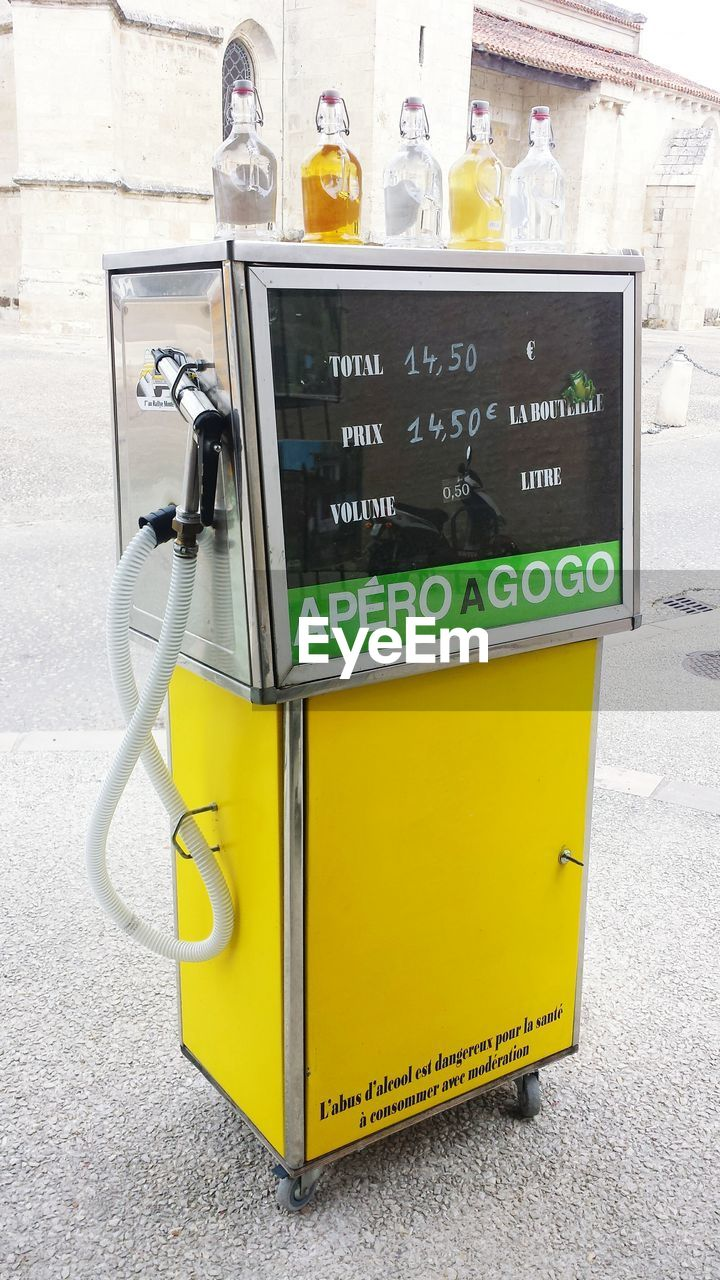 text, western script, communication, yellow, day, outdoors, no people, fuel pump, close-up