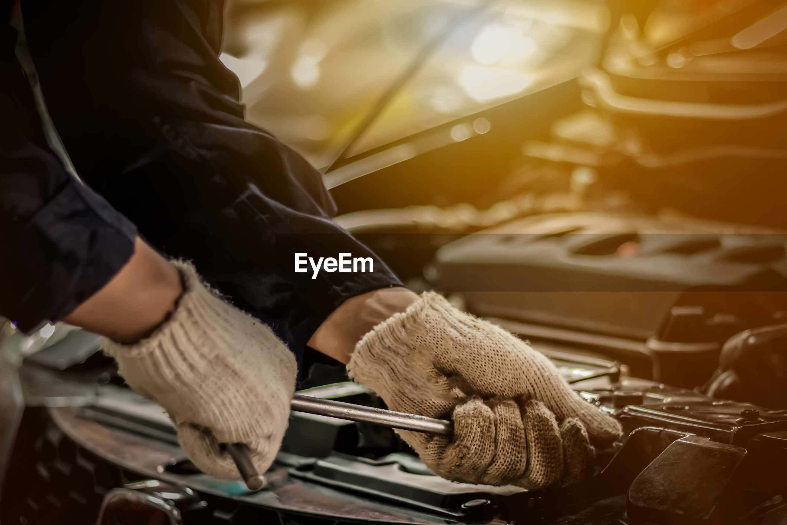 Midsection of mechanic repairing car