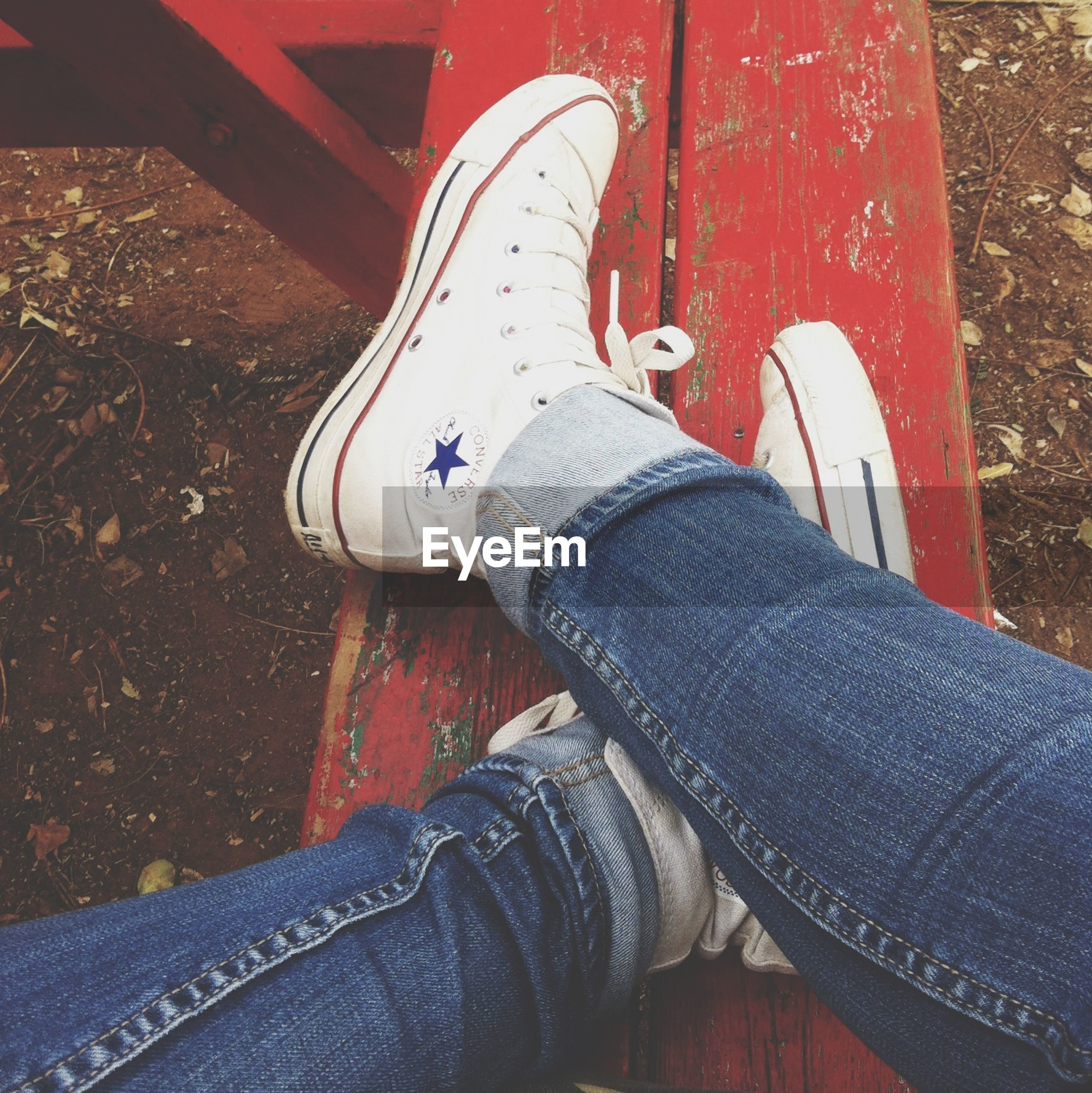 low section, person, shoe, jeans, footwear, personal perspective, human foot, lifestyles, high angle view, standing, sitting, canvas shoe, part of, relaxation, leisure activity, legs crossed at ankle, close-up