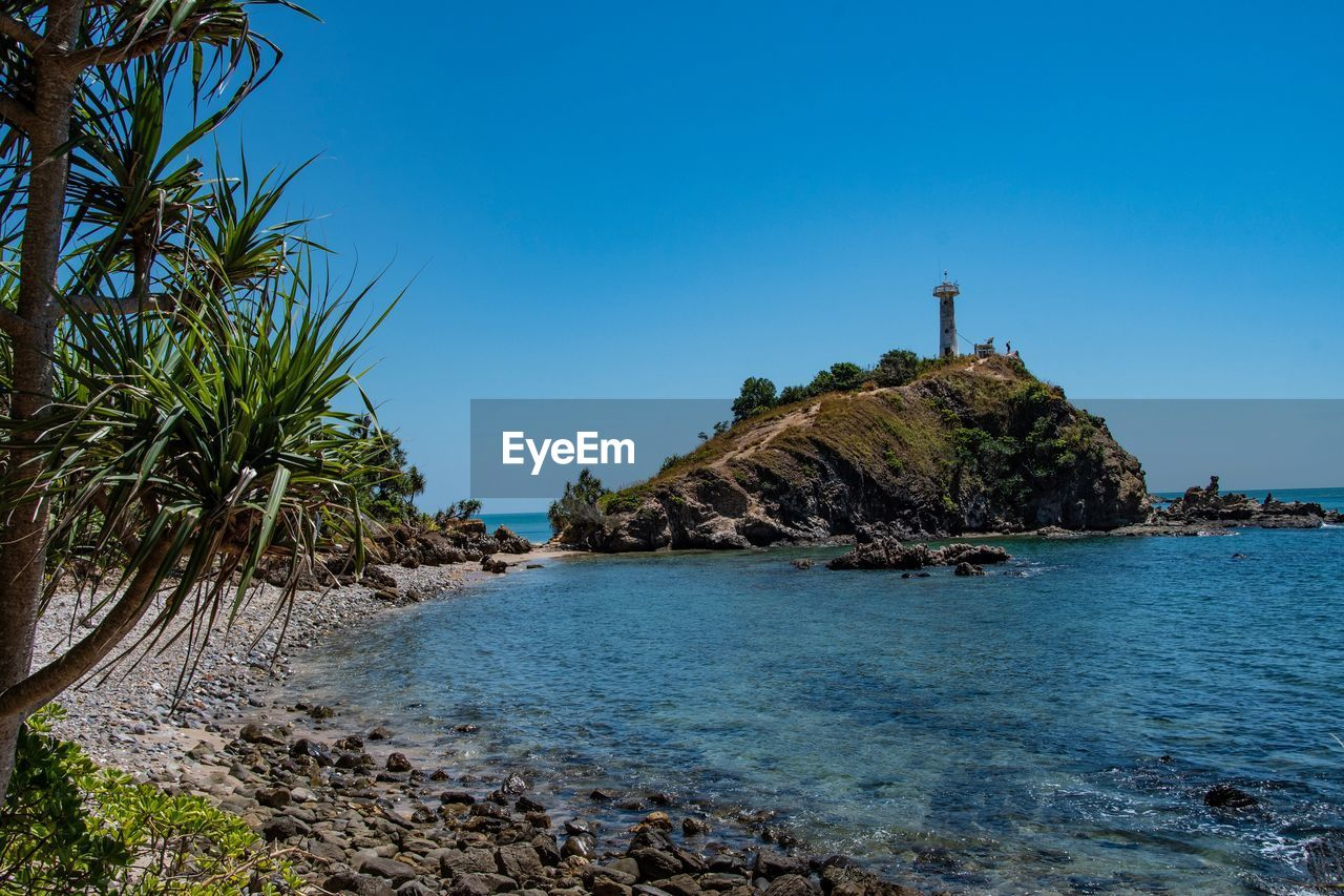 water, sea, sky, scenics - nature, beauty in nature, blue, land, tranquility, nature, rock, plant, beach, tranquil scene, clear sky, tree, day, no people, tropical climate, rock - object, guidance, lighthouse, outdoors