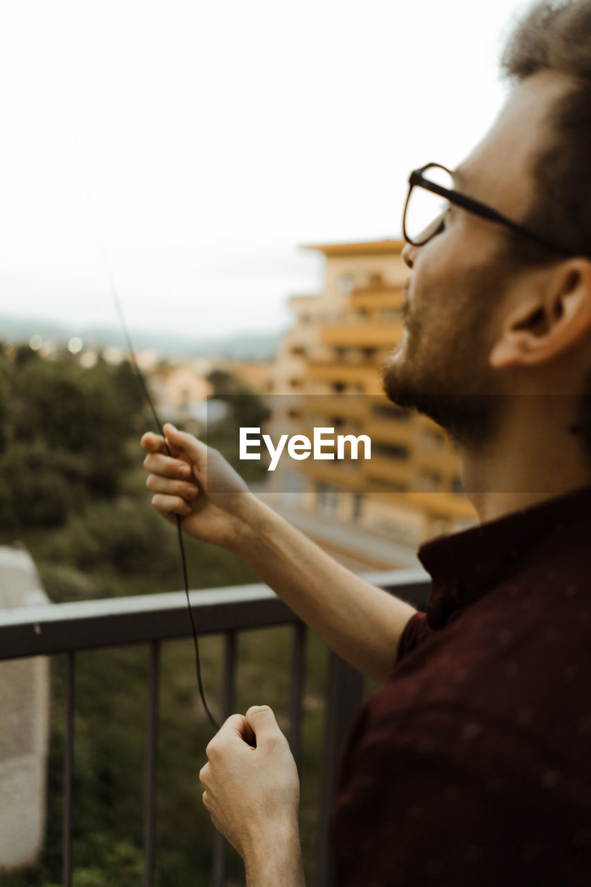 Young man with glasses trying to fly kite from his balcony.