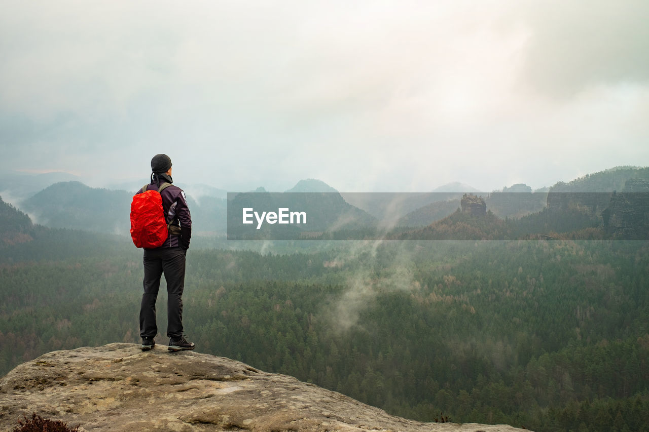 Red backpack and running suit man stands on top of a rock against background rocky foggy valley
