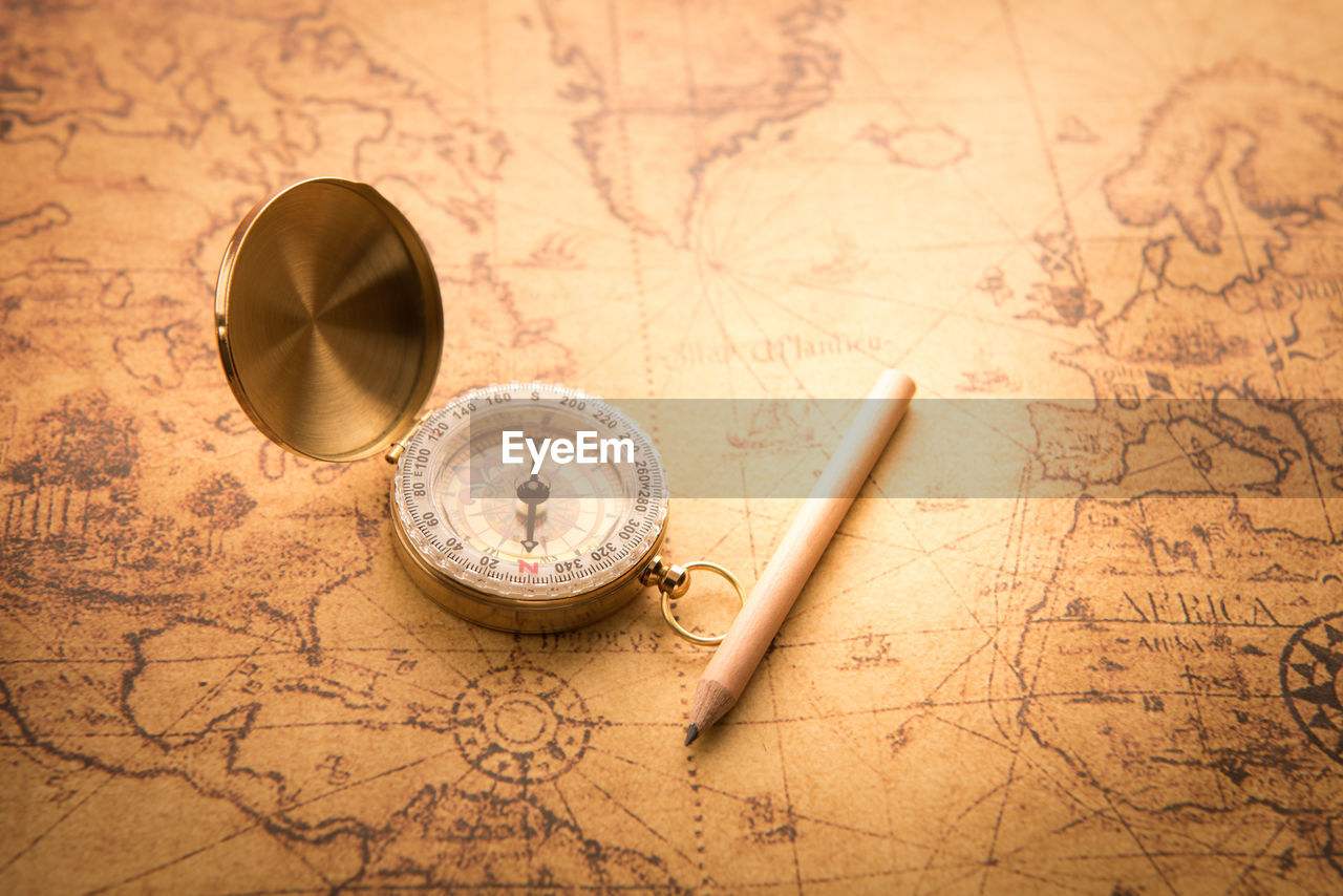 Close-up of navigational compass and pencil on map