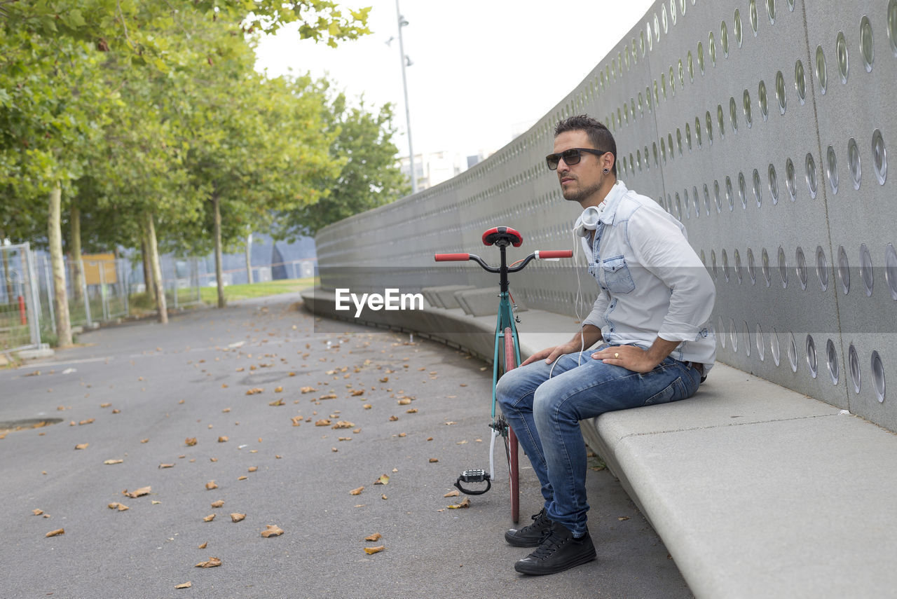 Man with bicycle sitting on seat by road