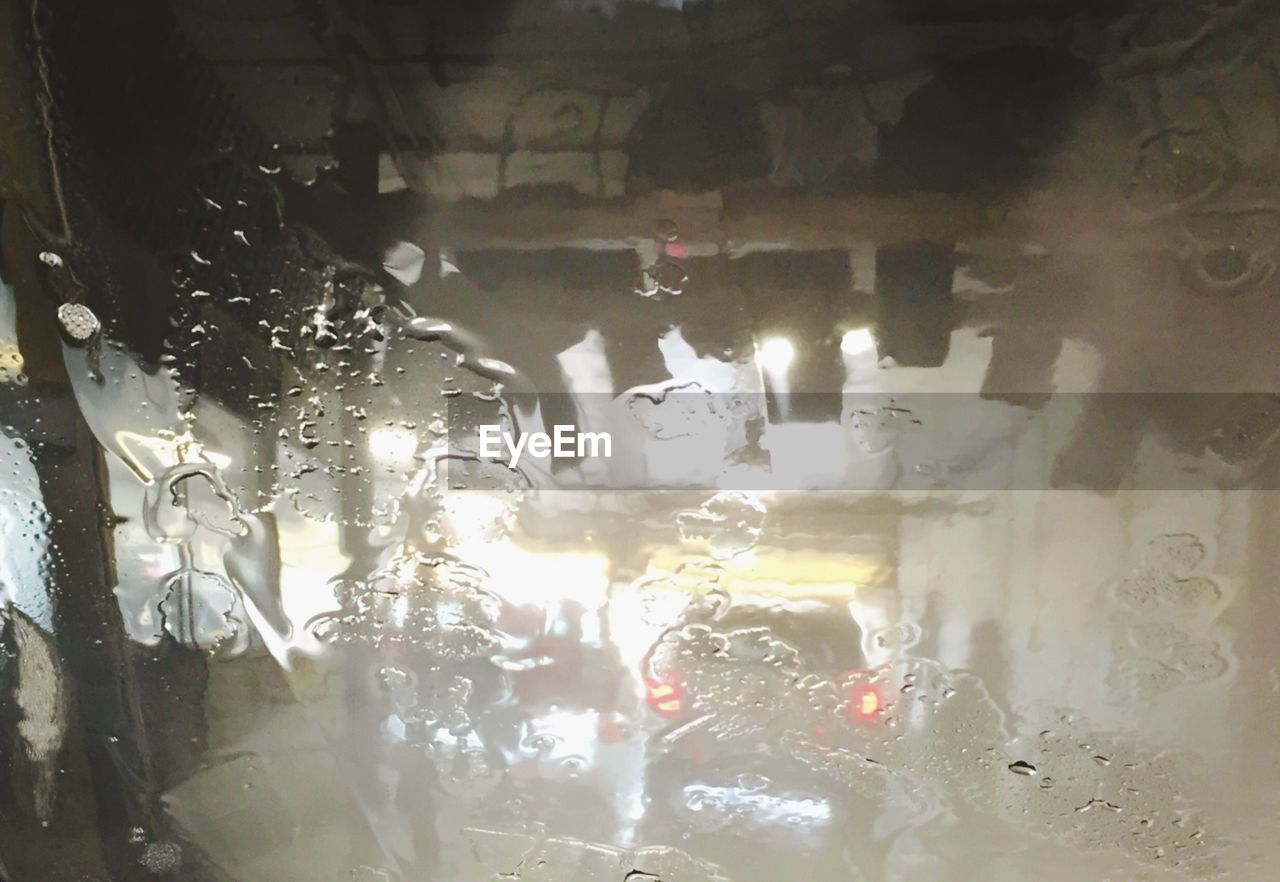 Illuminated lights seen through wet car windshield at night