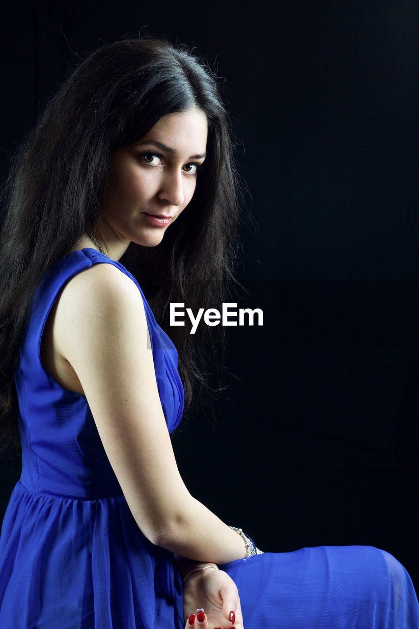 Portrait of beautiful female model in blue dress standing against black background
