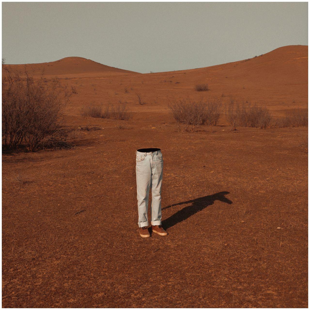 Man Standing On Sand In Desert Against Clear Sky