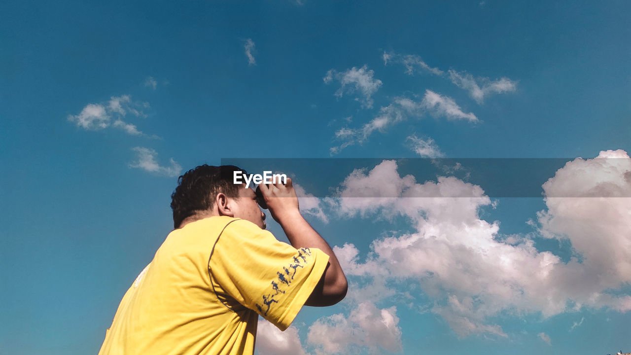 Rear view of man photographing against sky