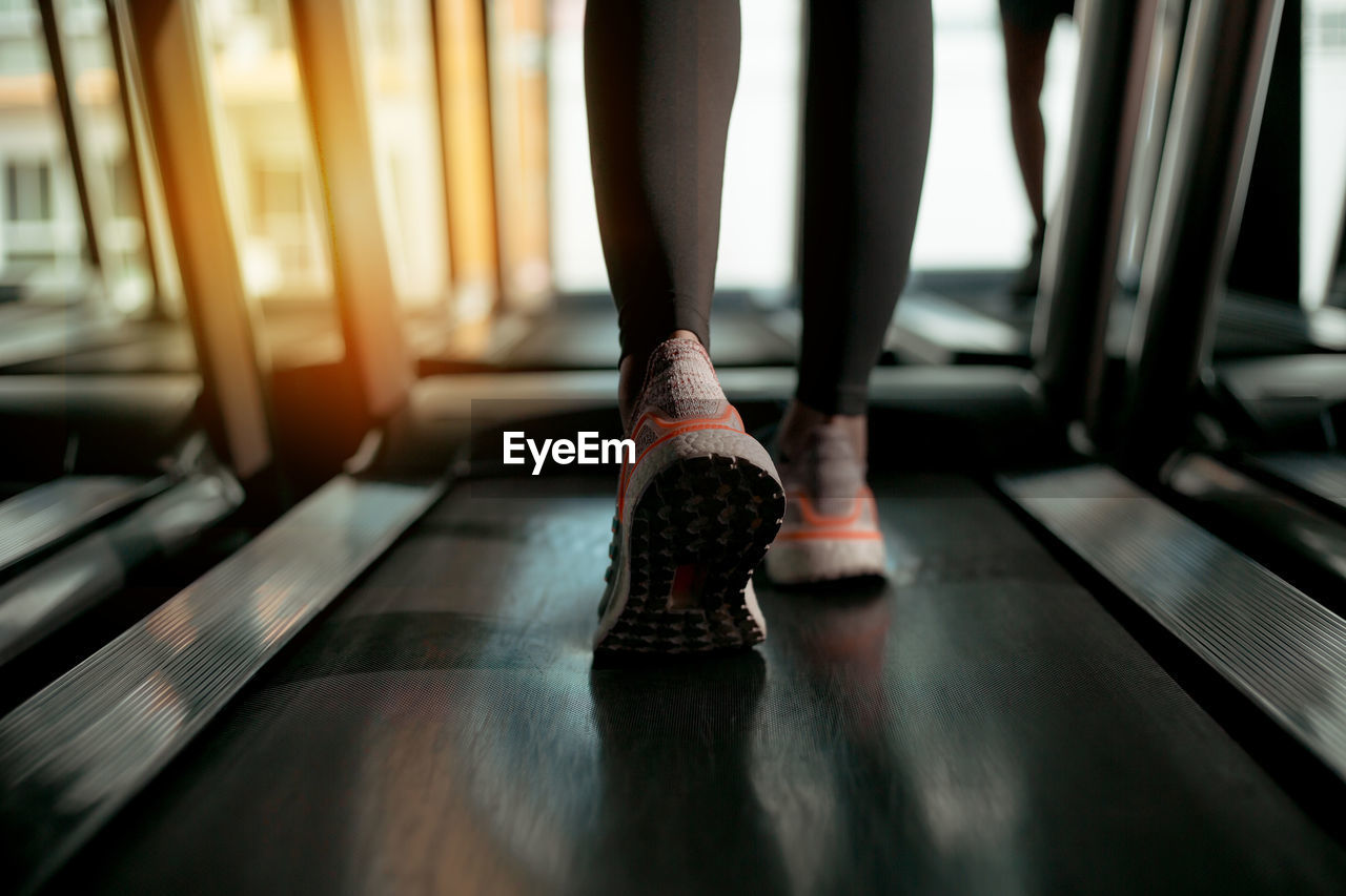 Low section of woman exercising on treadmill