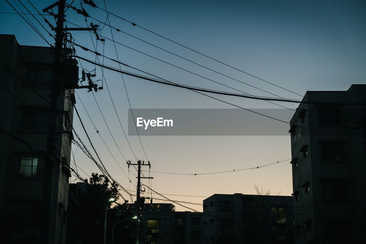 sky, electricity, architecture, cable, built structure, low angle view, technology, building exterior, connection, power line, nature, no people, electricity pylon, city, power supply, sunset, fuel and power generation, clear sky, building, dusk, outdoors, complexity, telephone line, electrical equipment