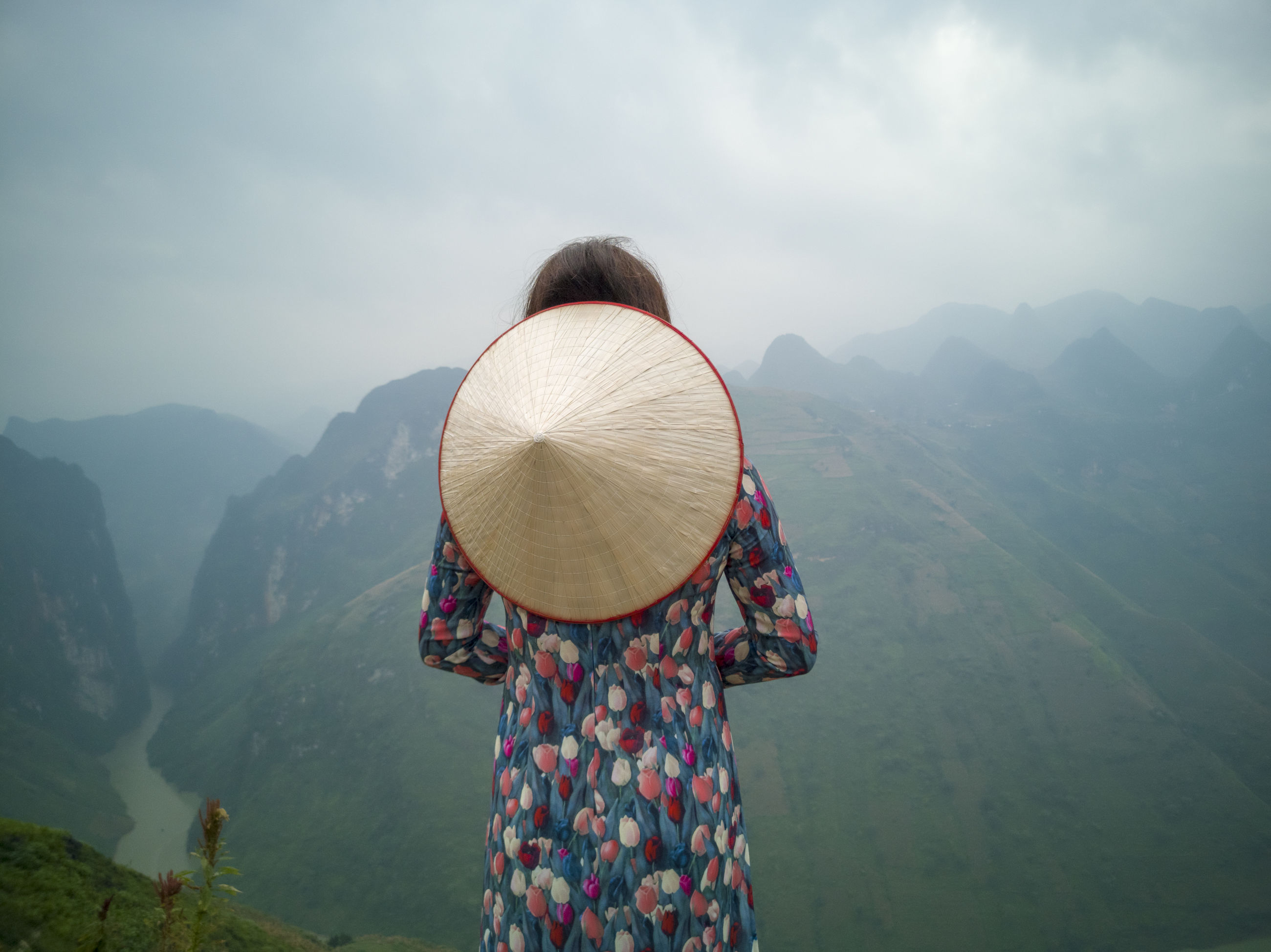 Rear view of woman with asian style conical hat standing against mountains in foggy weather