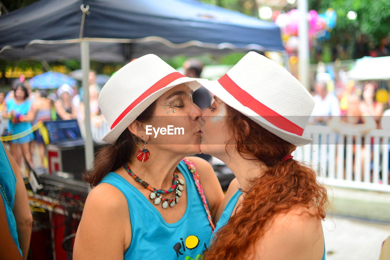 Close-up of lesbian couple kissing in city during event