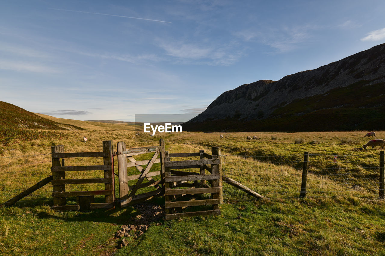 sky, landscape, boundary, barrier, fence, mountain, grass, field, land, nature, environment, cloud - sky, beauty in nature, tranquility, tranquil scene, scenics - nature, plant, rural scene, no people, non-urban scene, mountain range, outdoors, ranch