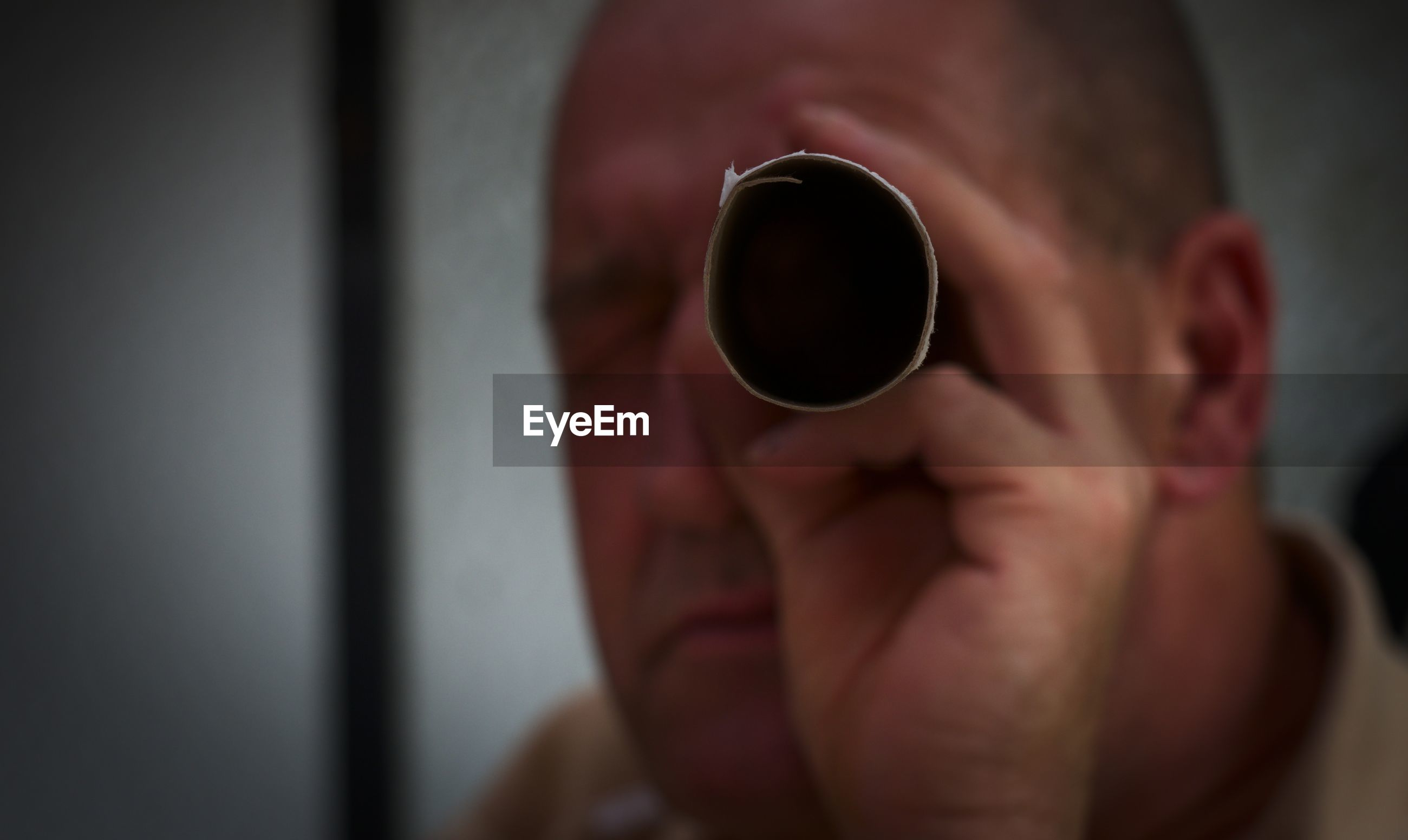 Close-up of man looking through paper roll