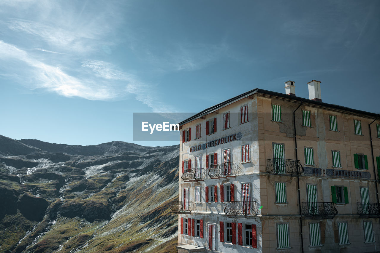 sky, building exterior, built structure, architecture, cloud - sky, building, mountain, nature, no people, residential district, day, window, outdoors, low angle view, scenics - nature, city, mountain range, beauty in nature, house, tranquil scene