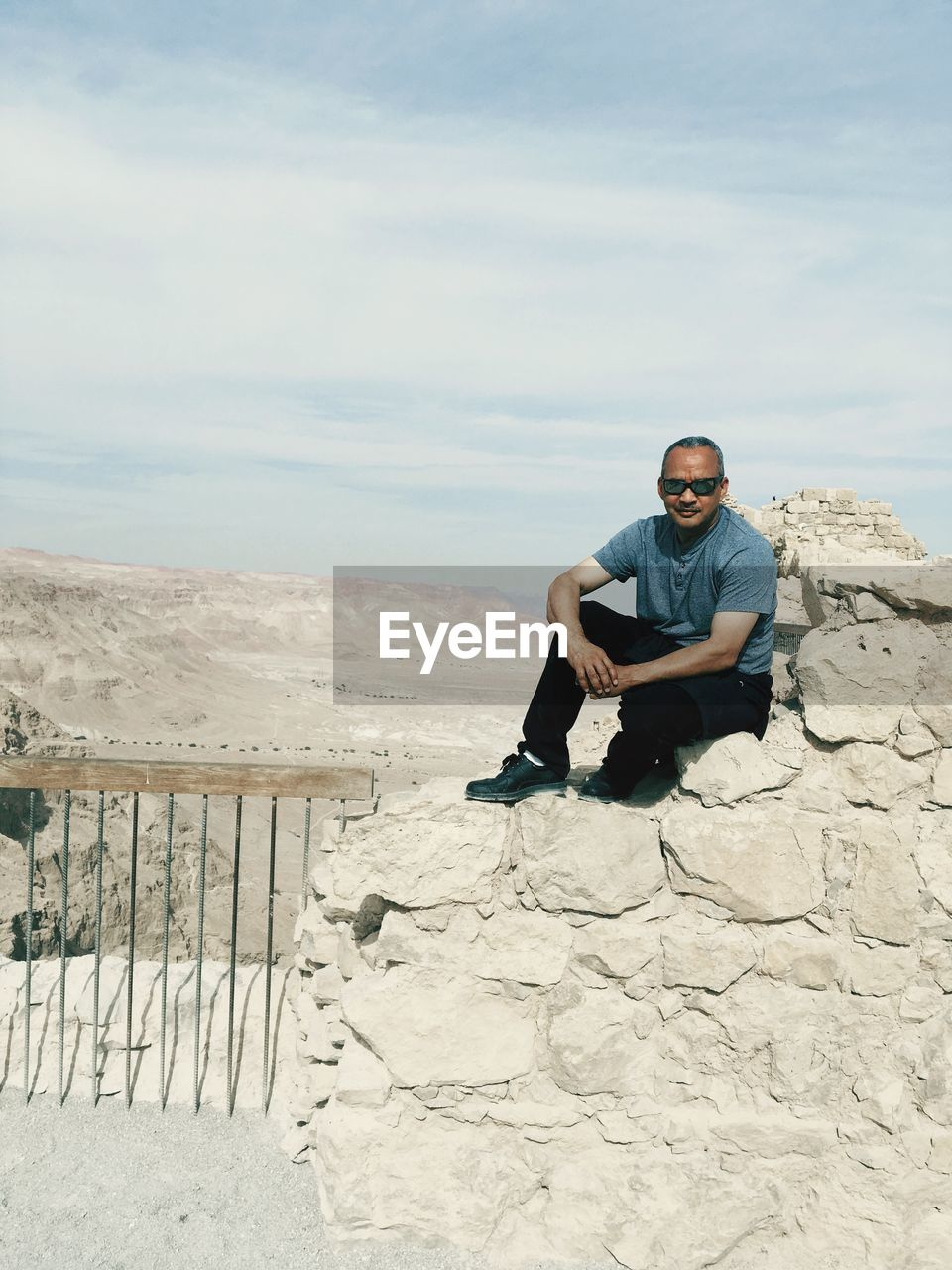 Man Wearing Sunglasses While Sitting On Rock Against Sky