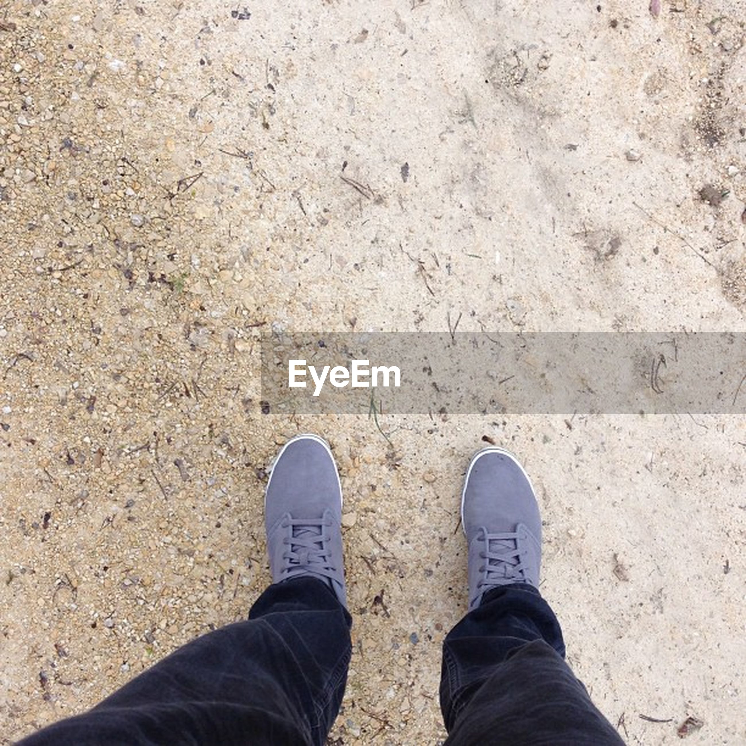 low section, shoe, person, personal perspective, standing, men, lifestyles, high angle view, jeans, footwear, human foot, unrecognizable person, leisure activity, field, day, outdoors, sand