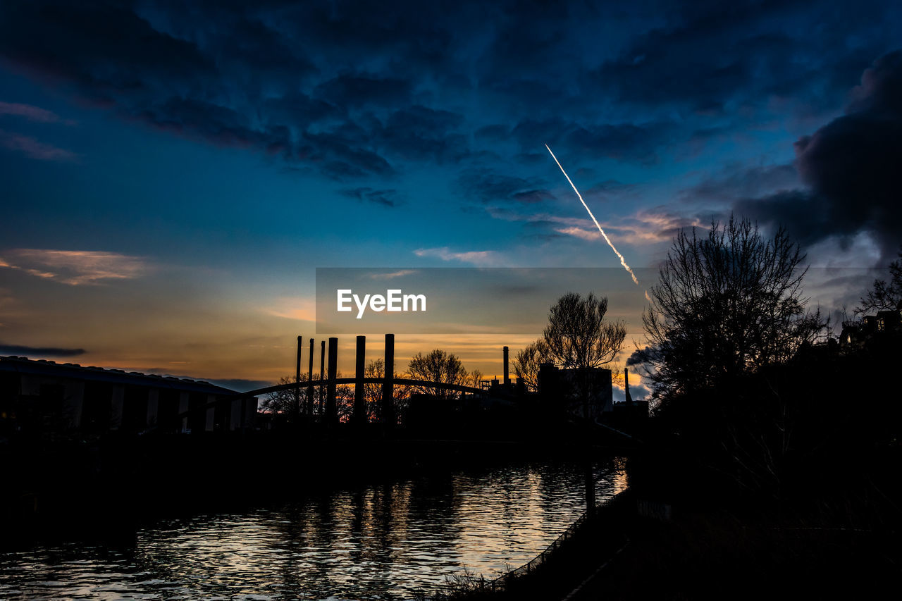 sky, cloud - sky, water, architecture, built structure, nature, building exterior, sunset, river, silhouette, bridge, connection, no people, bridge - man made structure, transportation, outdoors, tree, vapor trail, beauty in nature