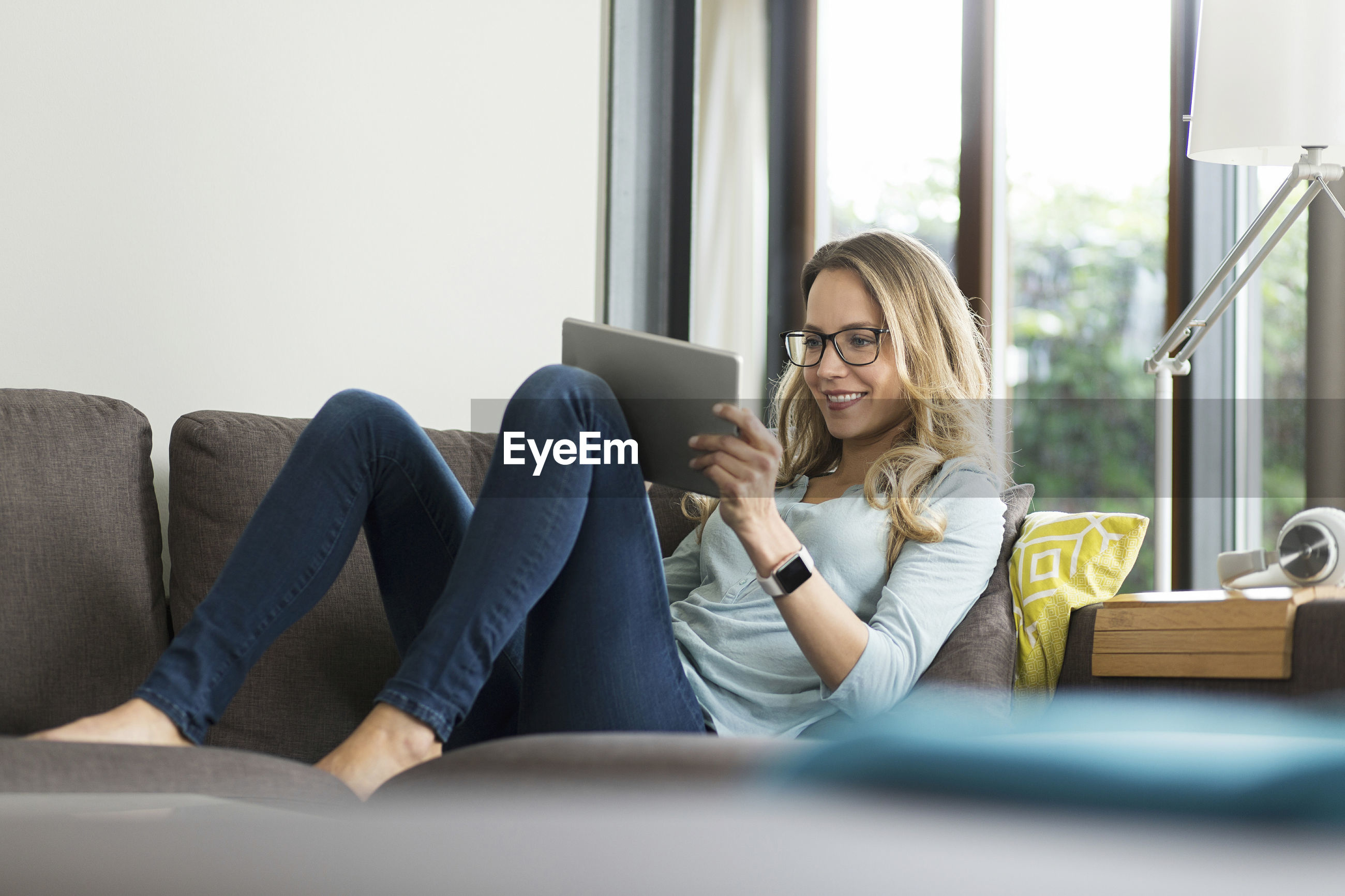 HAPPY YOUNG WOMAN USING PHONE WHILE SITTING ON SOFA AT HOME