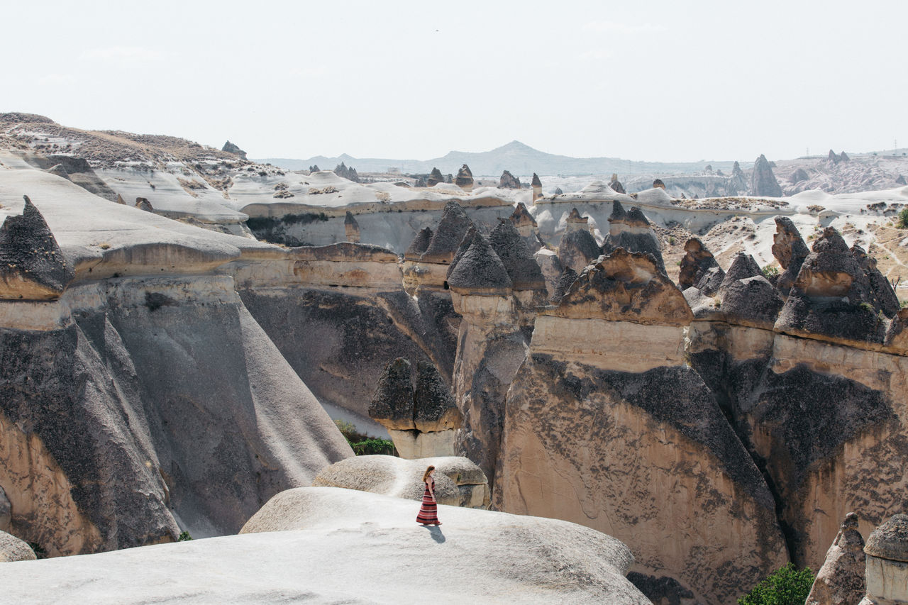 High Angle View Of Woman Standing On Cliff Against Rock Formations