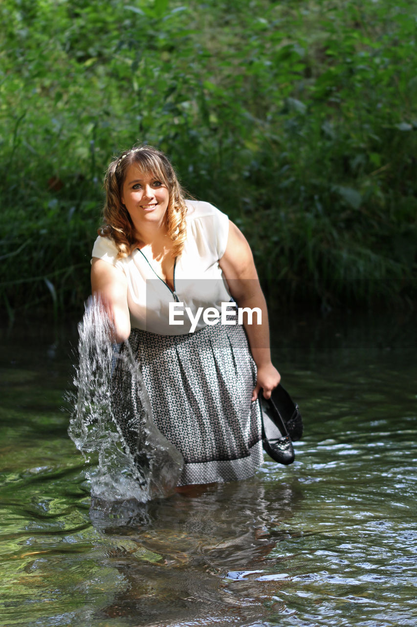 Young Woman Splashing Water While Standing In River Against Plants