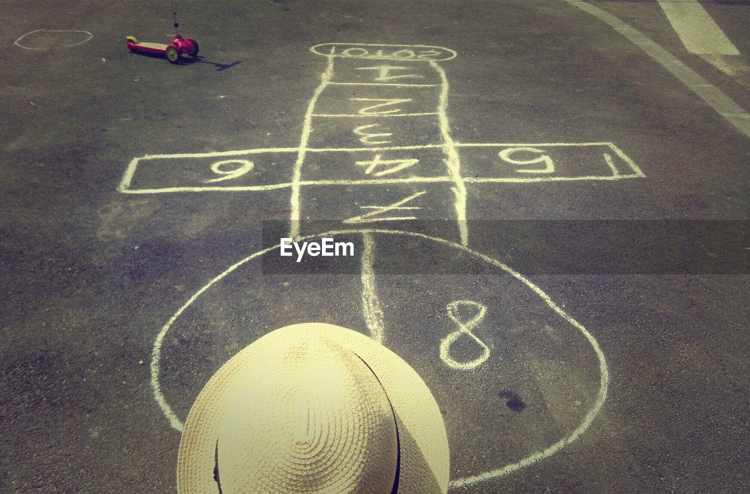 Child playing hopscotch on street
